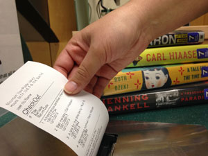 Hand holding checkout receipt with books behind